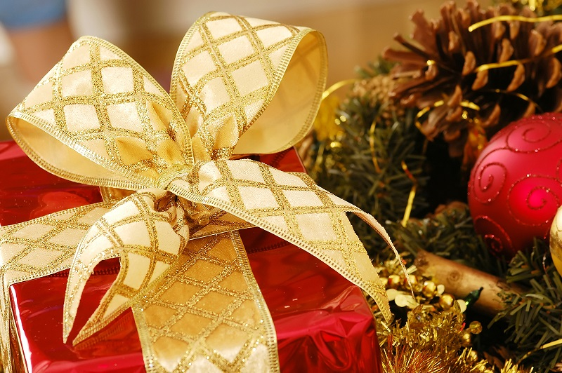 A festive image showing a present wrapped in red and tied with a gold ribbon