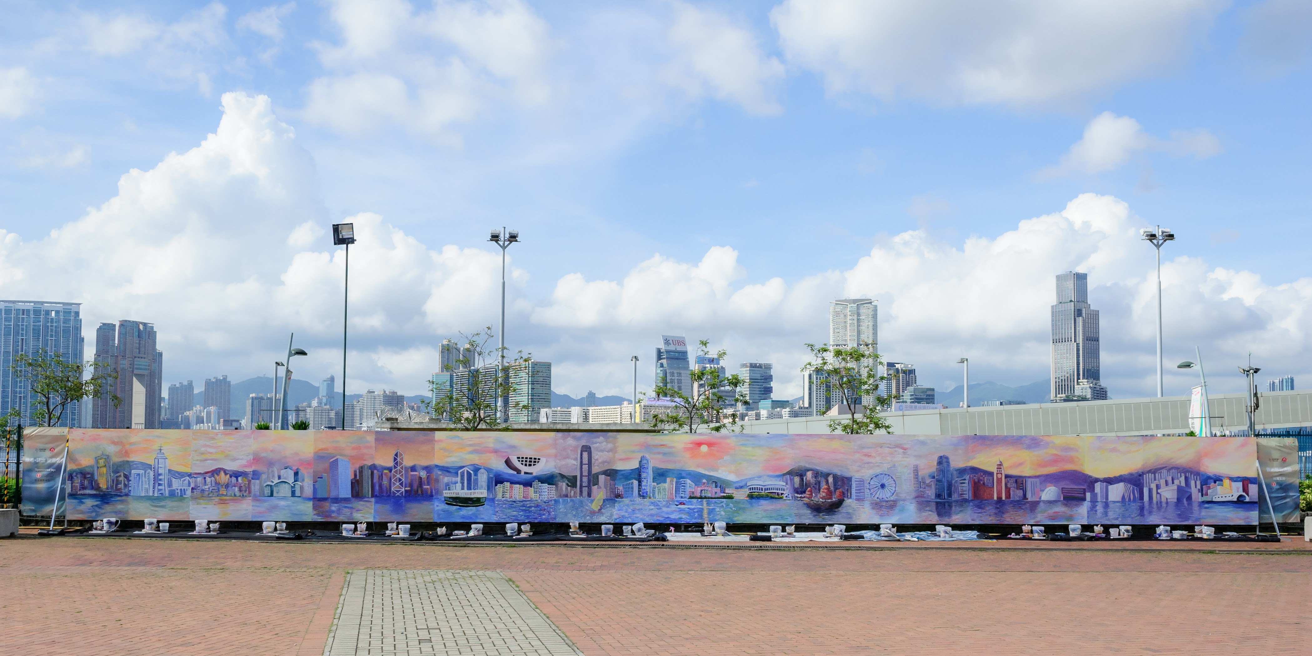 這幅80尺長的巨型壁畫名為「維港‧日出」,現在中環海濱活動空間舉行的「中環夏誌」活動中展出。